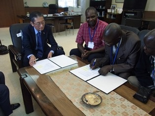 Grant Contract signing by H.E. Mr. Terada (left) and Mr. John Orek, Chairman of Mulambo Self Help Group (right)