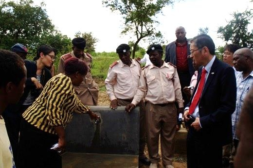 Ambassador Terada receiving explanation about the water tap which is piped from the dam