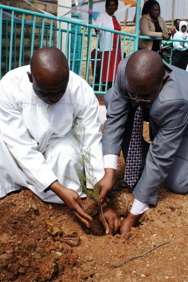 Father Regilio Kirimi, Representative of the Bishop, planting a tree to commemorate the occasion